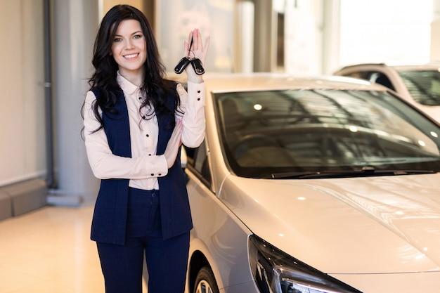 Szczęśliwa kobieta kupujący possing z kluczami w pobliżu jej nowego pojazdu w salonie samochodowym