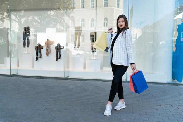 Szczęśliwa kobieta kupujący z wielobarwnymi torbami na zakupy na tle prezentacji.