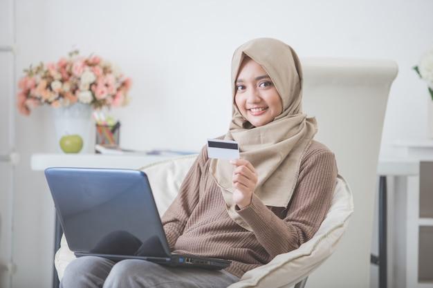Szczęśliwa kobieta kupuje produkt przez zakupy online.