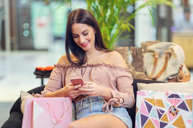 Szczęśliwa kobieta kupuje ubrania w sklepie