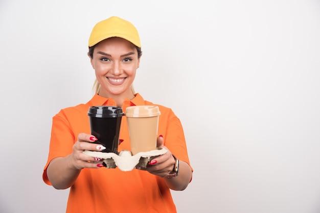 Szczęśliwa kobieta kurier trzyma dwie filiżanki kawy na białej ścianie.
