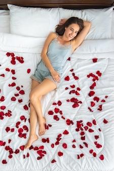 Szczęśliwa kobieta leżąc na łóżku z płatkami róż. widok z góry