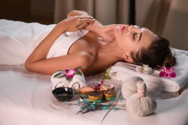 Szczęśliwa kobieta, leżąc na stole z flowrs, ręcznik po zabiegach spa