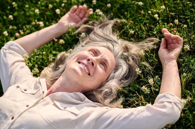 Szczęśliwa kobieta leżąca na zielonym trawniku