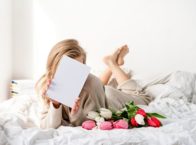Szczęśliwa kobieta leży na łóżku w piżamie, trzymając bukiet kwiatów tulipanów i pustą kartę do makiety projektu
