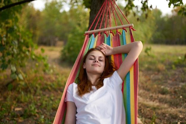 Szczęśliwa kobieta leży w hamaku na świeżym powietrzu w lesie, śmiejąc się