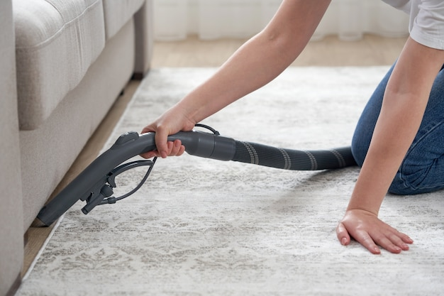 Szczęśliwa kobieta lub gospodyni domowa z odkurzaczem do czyszczenia podłogi pod kanapą w domu