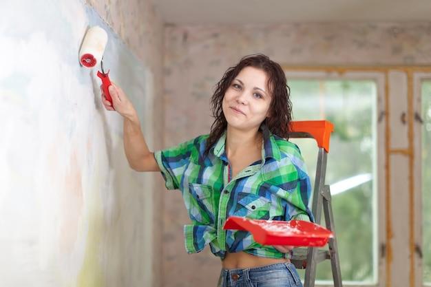 Szczęśliwa kobieta maluje ścianę