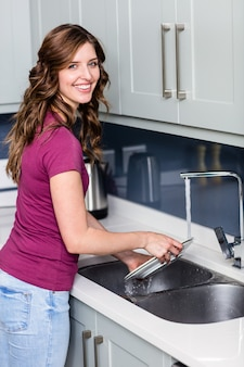 Szczęśliwa kobieta mycie talerzy