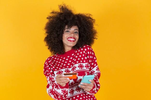 Szczęśliwa kobieta na boże narodzenie pokazując plastikową kartę kredytową trzymając telefon komórkowy