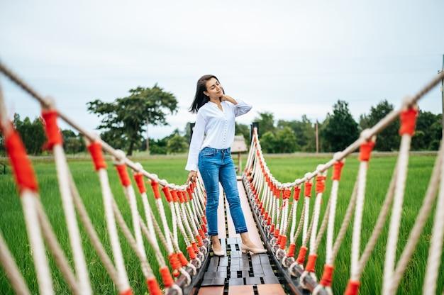Szczęśliwa kobieta na drewnianym moście w zielonej łące w słoneczny dzień