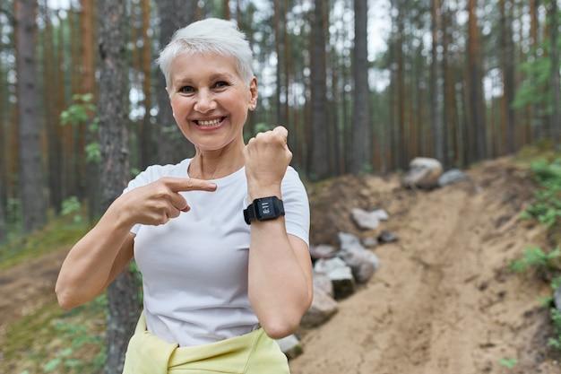 Szczęśliwa kobieta na emeryturze w odzieży sportowej, uśmiechając się szeroko, wskazując na wyświetlacz inteligentnego zegarka na nadgarstku