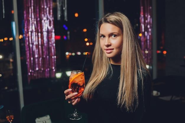 Szczęśliwa kobieta na imprezie, uśmiechając się i trzymając koktajl.