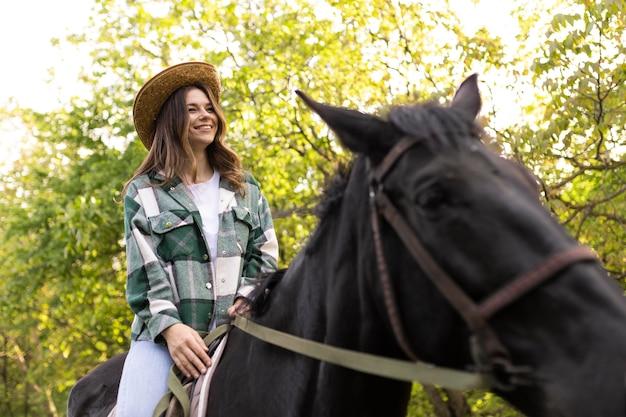 Szczęśliwa kobieta na koniu na zewnątrz