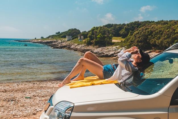 Szczęśliwa kobieta na morzu lato plaża siedzi na koncepcji wakacji maski samochodu