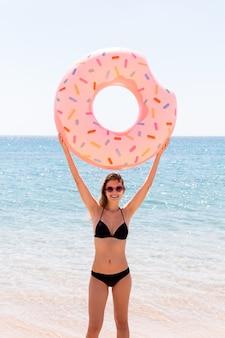 Szczęśliwa kobieta na plaży bawi się nadmuchiwanym pierścieniem pączka. letnie wakacje i koncepcja wakacji.