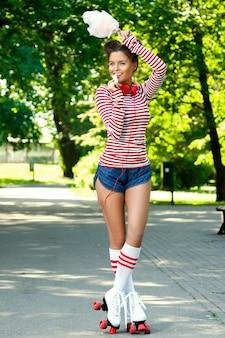Szczęśliwa kobieta na rolkowej łyżwie w parku