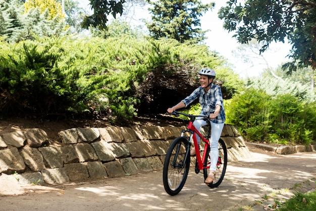 Szczęśliwa kobieta na rowerze w parku
