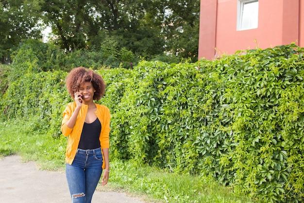Szczęśliwa kobieta na ulicy rozmawia przez telefon