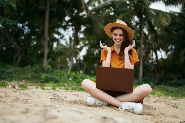 Szczęśliwa kobieta na wakacjach z laptopem piękny model
