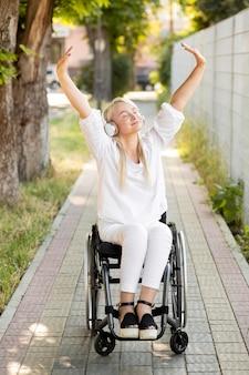Szczęśliwa kobieta na wózku inwalidzkim ze słuchawkami