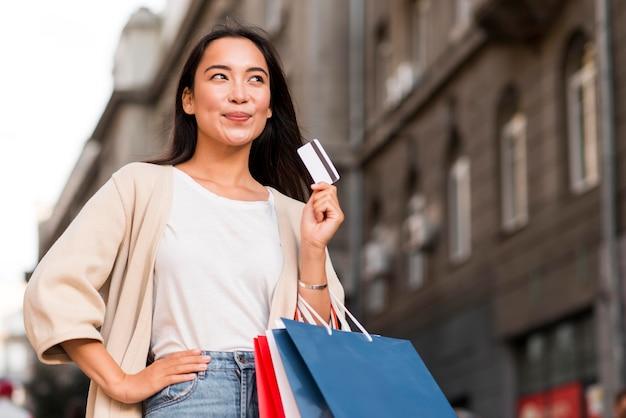 Szczęśliwa kobieta na zewnątrz trzymając torby na zakupy i kartę kredytową