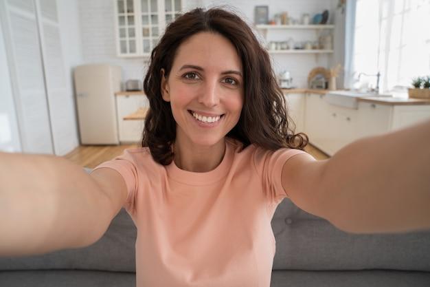 Szczęśliwa kobieta nagrywająca nowe treści do vloga wyciągająca rękę do aparatu fotografująca się w domu