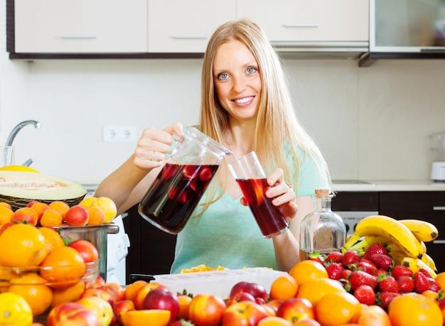 Szczęśliwa kobieta nalewania napojów z owocami