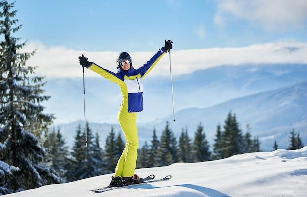 Szczęśliwa kobieta narciarz pozowanie na nartach