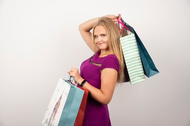 Szczęśliwa kobieta niosąc kolorowe torby na zakupy.