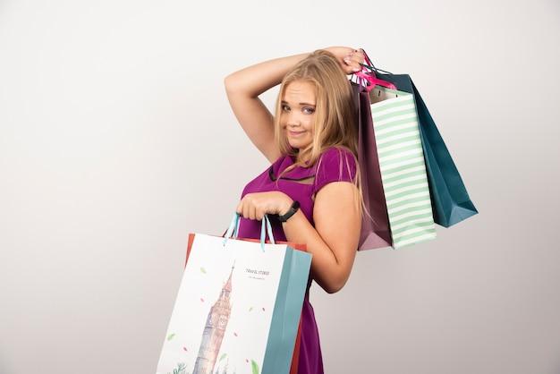 Szczęśliwa kobieta niosąca kolorowe torby na zakupy.
