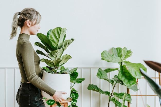 Szczęśliwa kobieta niosąca roślinę doniczkową