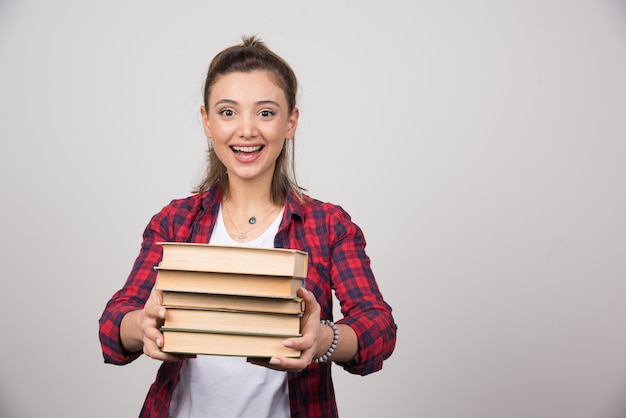 Szczęśliwa kobieta niosąca stos książek na szarej ścianie.