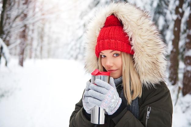 Szczęśliwa kobieta nosi ciepłe ubrania, picie gorącej herbaty