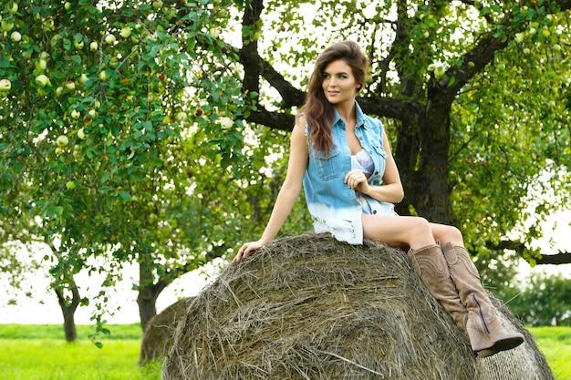 Szczęśliwa kobieta nosi dżinsową kamizelkę siedzi na stogu siana
