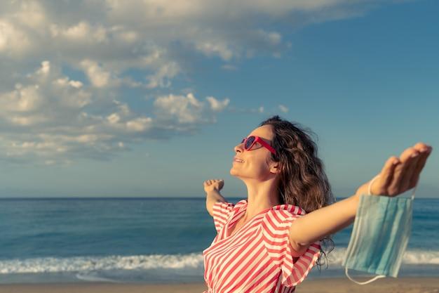 Szczęśliwa kobieta nosi maskę medyczną na zewnątrz na tle błękitnego nieba. osoba korzystająca z morza w lecie.