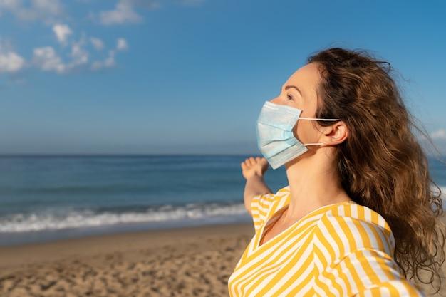 Szczęśliwa kobieta nosi maskę medyczną na zewnątrz na tle błękitnego nieba