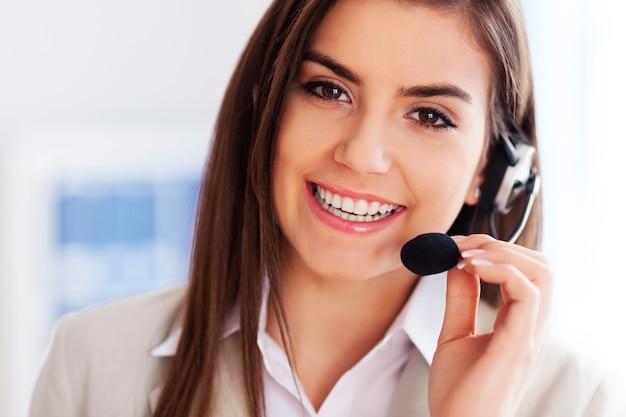 Szczęśliwa kobieta nosi zestaw słuchawkowy i szuka