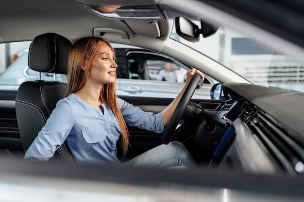 Szczęśliwa kobieta nowy właściciel samochodu siedzi na siedzeniu kierowcy i rozglądając się
