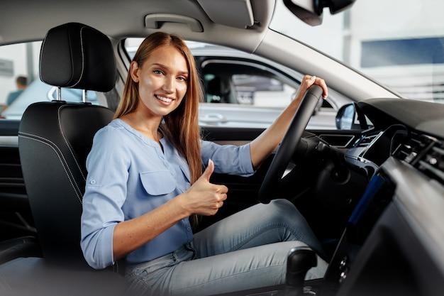 Szczęśliwa kobieta nowy właściciel samochodu siedzi na siedzeniu kierowcy