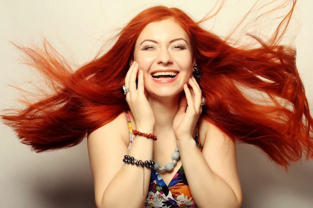 Szczęśliwa kobieta o długich rudych włosach