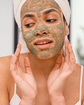 Szczęśliwa kobieta o domowej masce na twarzy