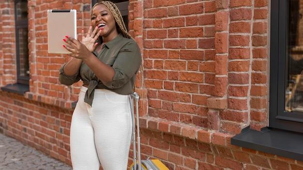 Szczęśliwa kobieta o rozmowie wideo na jej tablecie z miejsca na kopię