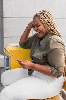 Szczęśliwa kobieta o wideokonferencji na jej tablecie podczas podróży