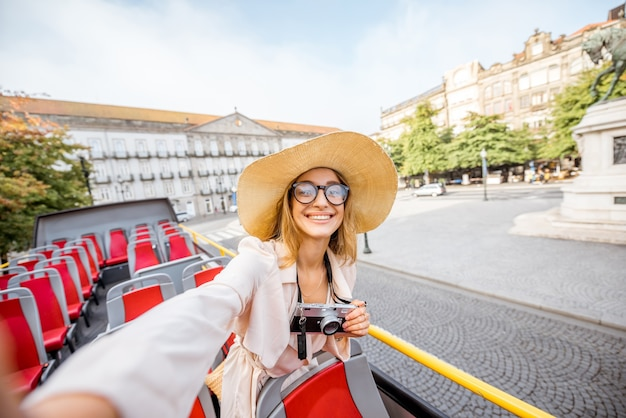 Szczęśliwa kobieta o wycieczce na otwartym autobusie turystycznym stojącym na placu wolności w mieście porto, portugalia