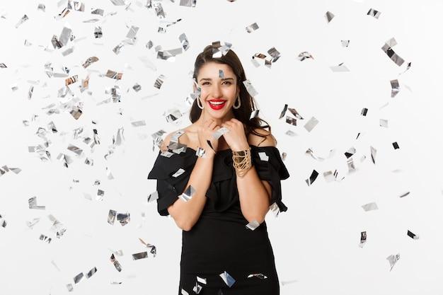 Szczęśliwa kobieta obchodzi ferie zimowe, uśmiechając się wesoło, imprezując na nowy rok z konfetti, stojąc na białym tle.