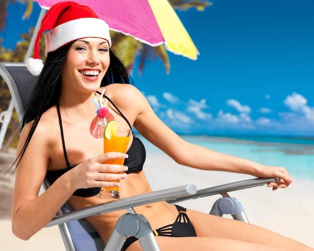 Szczęśliwa kobieta obchodzi nowy rok na plaży.