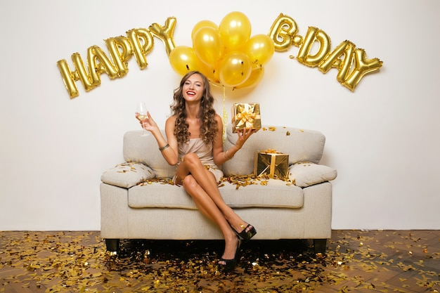 Szczęśliwa kobieta obchodzi urodziny w złotym konfetti, siedząc na kanapie