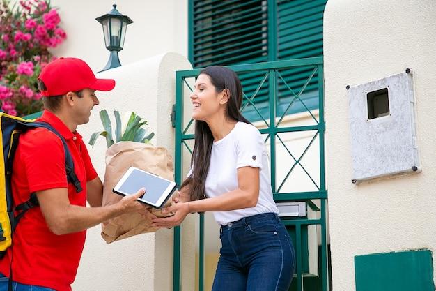Szczęśliwa kobieta odbiera jedzenie ze sklepu spożywczego, odbiera paczkę od kuriera przy jej bramie. koncepcja usługi dostawy lub dostawy