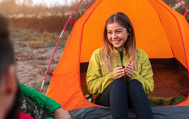 Szczęśliwa kobieta odpoczywa w pobliżu namiotu kempingowego z kubkiem gorącego napoju